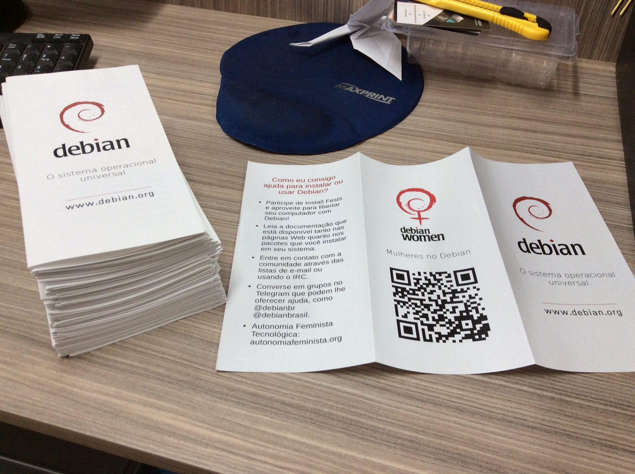 A pile with folded Debian Women folders. The writings are in Portuguese and it's possible to see a QR code.