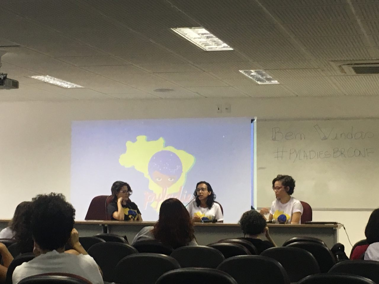 picture of PyLadiesBRConf. Three women sitting in front of a table, on stage, speaking