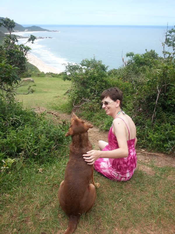 Renata's picture, a white woman sitting on the grass, overlooking the beach below. She pets a brown stray that sits next to her