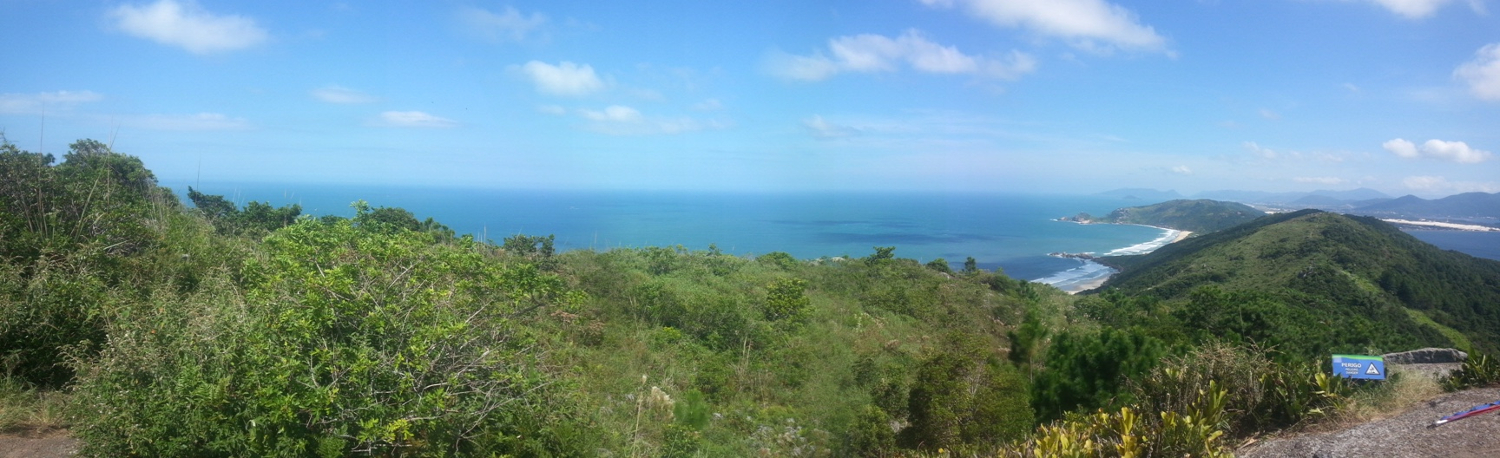 Photo taken from the top of a hill, overlooking light green ocean beaches